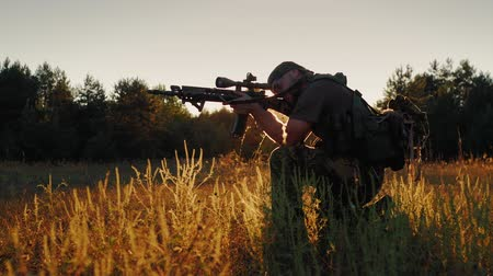 guerrilla : Armed men in camouflage. It takes aim at the optical sight. On the Sunset Stock Footage