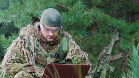 komutan : Portrait of military man sitting in the woods, dressed in camouflage. It uses laptop