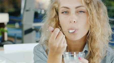 ложка : Attractive young woman eating ice cream in cafe, smiling at the camera