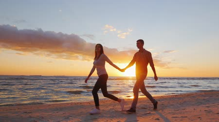 Steadicam slow motion shot: Romantic couple walking on the beach at sunset, holding hands, having a good time Vídeos