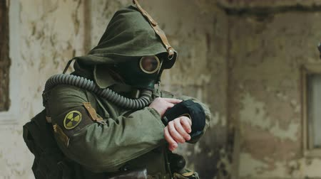 stalker : A man in an abandoned building looking at the readings on his arm. He was wearing a gas mask and protective suit. The sign of radioactive hazard on the sleeve Stock Footage