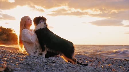 playing with a dog : Young woman playing with Australian Shepherd on the shores of a lake or the sea. The sun shines on the beautiful sunset in her hair