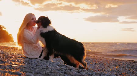 toco : I love my dog. Young blonde woman laskat sobbaku her, kisses her. Sit by the lake at sunset