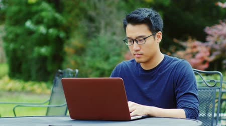 coffe : Asian man wearing glasses works with a laptop. Sitting on the summer terrace in the gardens or cafes. Stock Footage