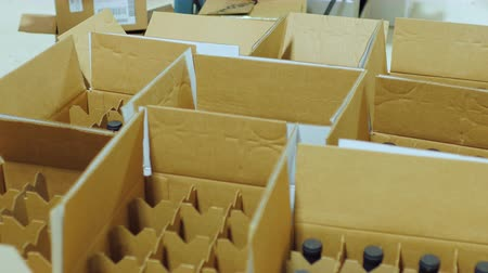 posta kutusu : Packaging bottle with alcohol. Work puts bottle of wine in cardboard boxes Stok Video