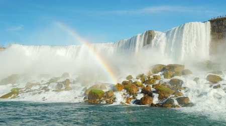 fall season : A huge rainbow in the background Niagara Falls. Lower angle shooting from the Niagara River