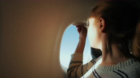 cadeira : Journey in an airplane. Young woman opens a window, spotrit the window, enjoying the flight
