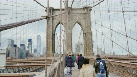 the suspension bridge : New York City, USA - OKTOBER, 2016: The pedestrian area of the Brooklyn Bridge. A crowd of tourists walking on the background of New York