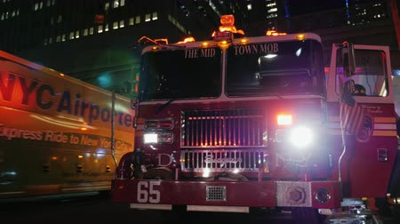 fire officer : New York, USA - OKT, 2016: The street is a fire truck with flashing lights activated. Passing by pedestrians