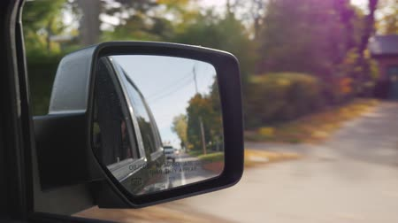 редакционный : Driving on a typical small American town. In the frame of the rear-view mirror. Clear autumn day, the sun gives beautiful reflections