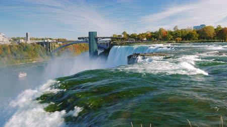 fall season : River and Niagara Falls. The powerful flow of water in the foreground . One of the most popular interest of New York - Niagara Falls