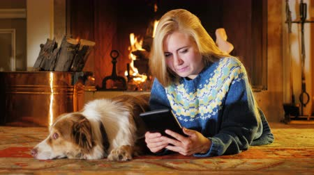 touchpad : A young attractive woman enjoys the tablet. In a comfortable house on a background of fire. Next to it is a dog Stock Footage