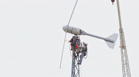 turbine : Two men working at high altitude. are repaired wind turbine. Near them is seen the boom of a crane Stock Footage