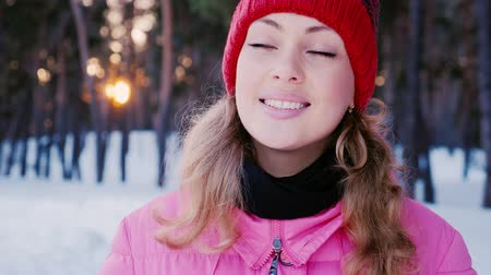 шляпа : Portrait of a young attractive caucasian woman in a winter forest. He is smiling at the camera at sunset background Стоковые видеозаписи