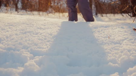 fur boots : Child Legs are on the virgin snow in the rays of the setting sun. Winter joy Stock Footage
