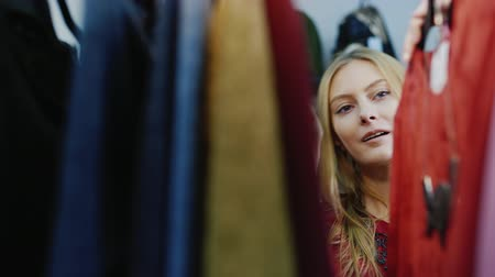clothing : Joyful shopping. Portrait of a young adult woman, looking at clothes on a hanger in the store womens clothing Stock Footage