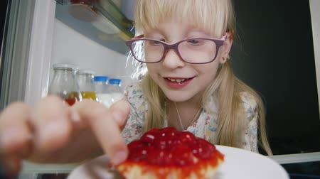 hűtőgép : A little girl secretly tastes a strawberry cake inside the refrigerator. Childhood pranks, happy childhood
