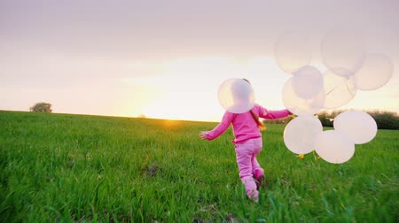 toco : Little girl in pink clothes with balloons. I play along the green meadow towards the sunset. Childrens dream, happy childhood