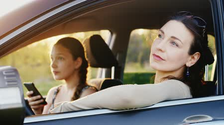 segítség : Mom and daughter 11 years old rest in the car in a picturesque place at sunset. A woman is looking at the car window, the girl is using the phone. Stock mozgókép