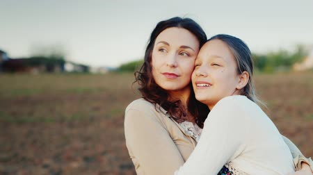 país : Mama gently hugs her daughter for 11 years. Together they look in same direction to the setting sun. Family values
