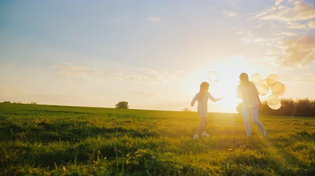 small park : Happy together. Young woman having fun with daughter. Running in a picturesque place, playing with balloons. Concept - childrens dreams, active and healthy lifestyle Stock Footage