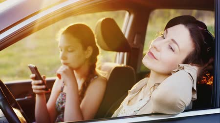 inside car : A young woman with her teenage daughter is spending time together. They sit in the car - my mother admires nature, my daughter uses a smartphone. Evening before sunset Stock Footage