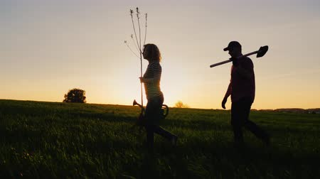 farm equipment : Steadicam shot: A young couple of farmers are walking along the field. They carry equipment for planting a tree. On the Sunset. Side view