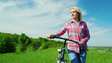 walking back : A young woman drives a bicycle through a green meadow. Idialistic landscape, beautiful spring colors