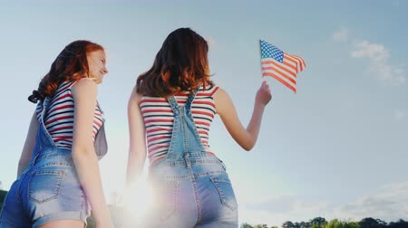 четверть : Two female twins with an American flag on a blue sky background. Back view. independence Day
