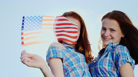 четверть : Portrait of twin girls with American flag. Looking at camera against the blue sky, smiling. independence Day