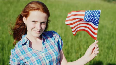 четверть : Attractive red-haired teenage girl with the American flag Стоковые видеозаписи