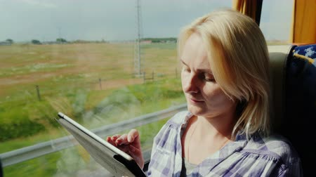 inside bus : A young woman travels by bus, enjoys a tablet. Outside the window is a picturesque area, the bus quickly rides