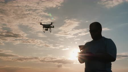 stable fly : pilot of the drone drives the copter at sunset, silhouette