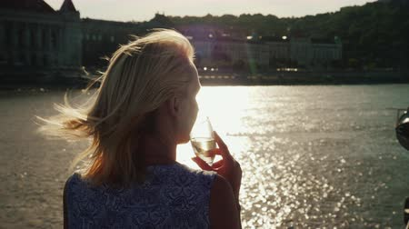круиз : Enjoy river cruises on the Danube. A woman with a glass in her hand looks at the shoreline of Budapest