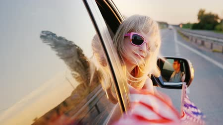 четверть : A fanny little girl in pink glasses looks out the window of the car. In his hand holds the American flag