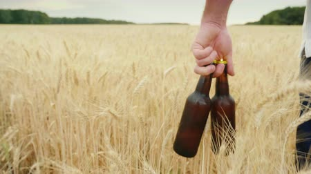 abridor : A man carries two bottles of cold beer over a field of barley. The concept is to quench your thirst