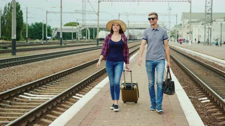 идущий : Young happy couple of tourists with travel bags go along the peron along the railroad. Beginning a great journey. Steadicam shot