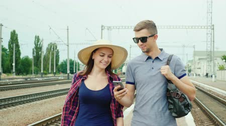 trilho : Happy young couple of tourists with a smartphone goes to the train station. Concept: order online tickets