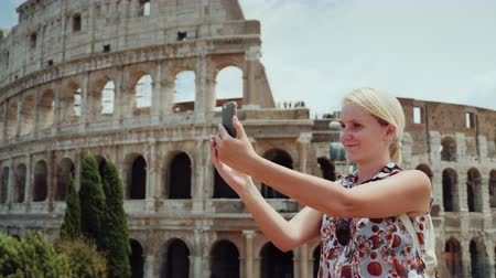 colloseum : A woman is photographed against the background of the famous Colosseum in Rome Stock Footage