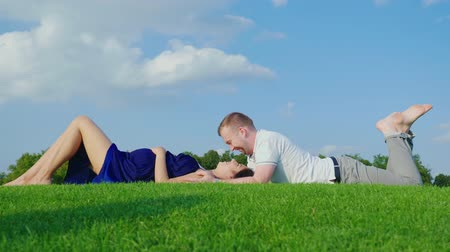 предназначенный только для мужчин : The young man gently kisses his pregnant wife. Together lie on a green lawn in a park against a blue sky Стоковые видеозаписи
