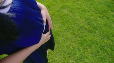 bare foot : A pregnant woman walks barefoot on the grass. Holds his hands on his belly. POV video