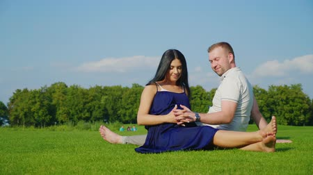 bumps : Young married couple in anticipation of a child. Together they rest in the park on the grass