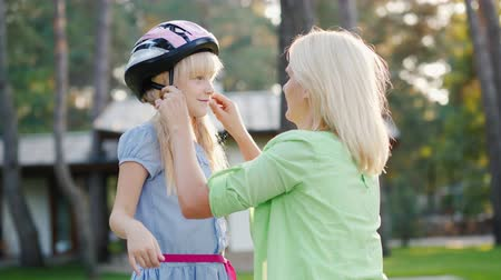 preocupações : Slow motion shot: Mom puts on a protective helmet for her daughter. Concept - care and safety