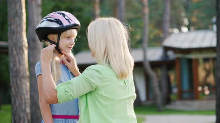 preocupações : Mom puts on a protective helmet for her daughter. Concept - care and safety Stock Footage
