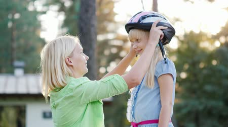 preocupações : A happy mother wears a protective helmet for her 6 years old daughter. The care and protection of parents concept
