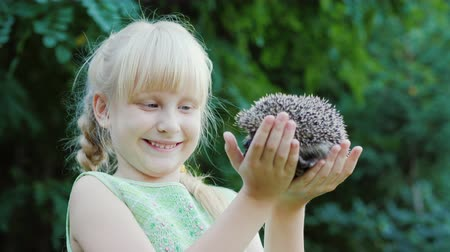 prickly : Happy blonde girl holding a hedgehog. Protection and care of animals concept Stock Footage