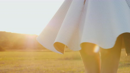 oneself : A young slim woman in a light skirt is spinning in a meadow. At sunset, slow motion video Stock Footage