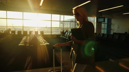 Войти : Young business woman with a travel bag and tablet going along the airport terminal. At sunset. Steadicam shot