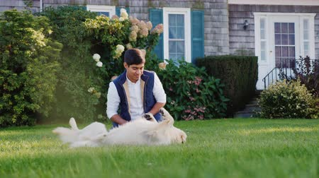 лабрадор : A young Indian man is playing with a dog in his backyard. Favorite pet