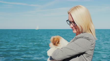 to be alone : A woman is holding a puppy in her arms against the background of the sea. Yachts can be seen in the distance Stock Footage